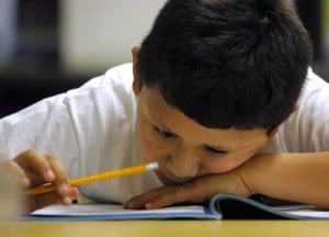 391429 06: A young student in Ms. McFaul''s second grade Early Intervention Bilingual class looks closely at a math exam during a summer school June 3, 2001 at Brentano Academy in Chicago. More than half of Chicago''s 430,000 public school students must attend summer school this year before they can go on to the next grade, Chicago Public School officials say. Former Chicago schools chief Paul Vallas said about 245,000 pupils failed to score high enough on the Iowa Tests of Basic Skills to be promoted. (Photo by Tim Boyle/Getty Images)